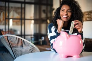 woman smiling with piggy bank